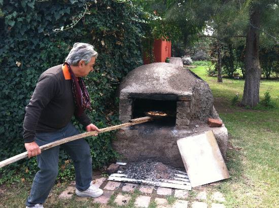 Bodega Familia Antonietti: Andres removes the empanadas from the clay oven