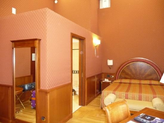 Hotel Livingston: L-shaped room with Queen bed and fabric walls.