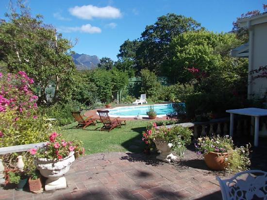 Ballot's House Guest Lodge: View of garden and pool and tennis court in the distance