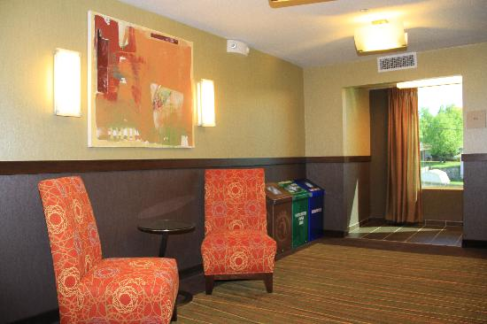 Hilton Garden Inn Springfield: Elevator lobby on each floor has bright colored accent chairs, a window and trash bins.