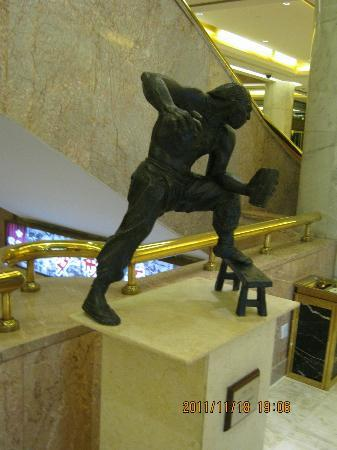 ‪بكين رينبو هوتل: One of the statues in the foyer, a martial art using a stool.‬