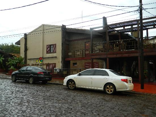 Passaro Suites Hotel: frente del hotel con coches de pasajeros