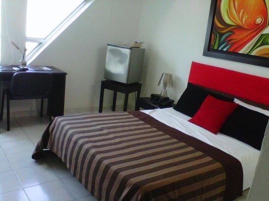 Monteria, Colombia: Cama, nevera y mesa auxiliar vista desde la entrada de la habitación