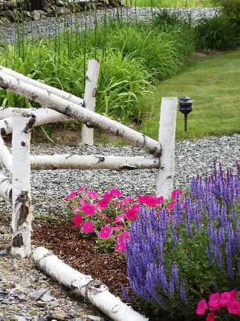 Lodge at Moosehead Lake: Birch fence & flowers around the Lodge