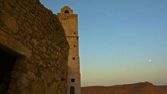 Tataouine, Tunisia: Moonrise over the mosque just outside cave dwellings that are now Hotel Gite