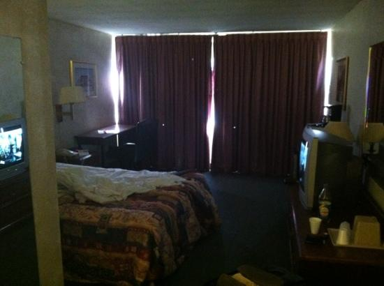 Seattle Pacific Hotel: small, bare bedroom. those are holes in the curtains