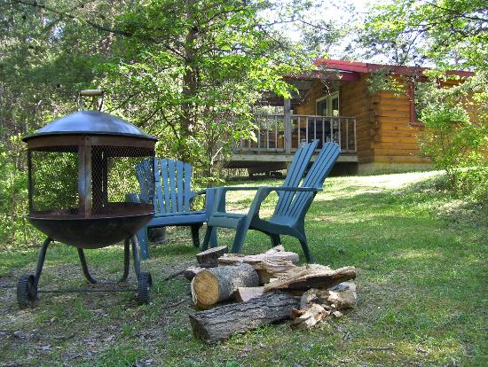 Getaway Cabins: Fire pit and chairs next to the cabin.