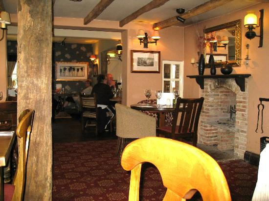 The Oystercatcher: Beamed ceilings and a log fireplace on the right.