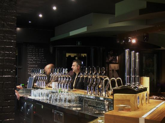 Montebelluna, Italia: il bancone da 15 spine e 3 pompe...sullo sfondo la parete lavagna in costante aggiornamento!!