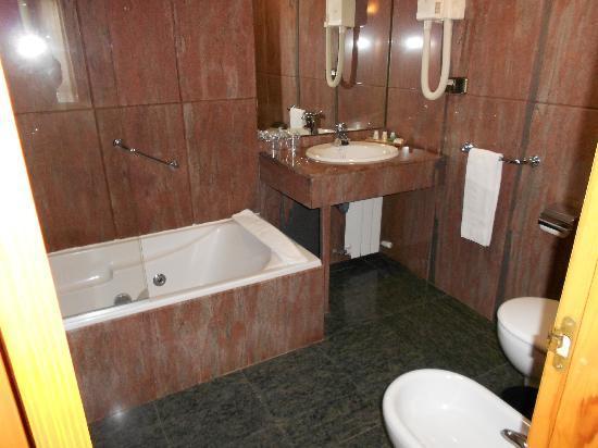 Hotel Alcazar -- Segovia: Bathroom, walls completely done in red granite, comfortable tub