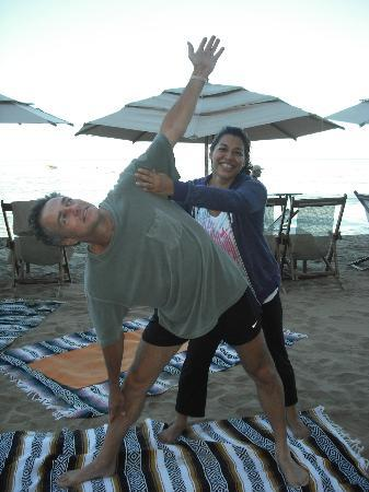 "Yoga Vallarta: Author of ""Buy A Million Dollars"" Greco Garcia in a beach yoga class with YV graduate Erika."