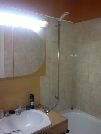 Hotel Du Commerce : douche non amovile, haut armoire ouverte sur néon