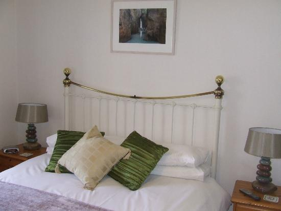 Trelew Farm : A warm, comfortable bedroom. I loved the photo above the bed of a local, Cornish scene.