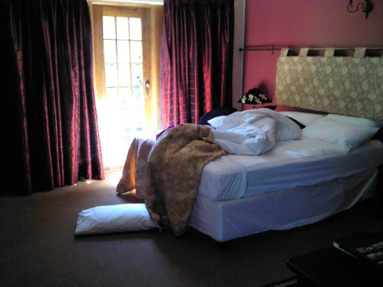 Village Green Guest House: the big bed in the room that also has french doors that lead out into the garden
