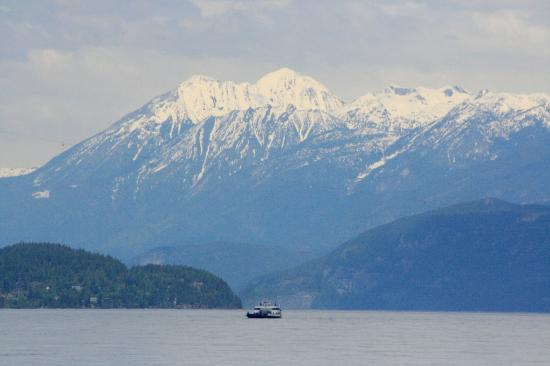 Kootenay Lake Ferry: Snowcapped peaks of the Selkirk Mountains loom high above a ferry on Kootenay Lake