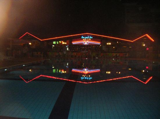 ‪كلوب تركويز أبارتمنتس: swimming pool and bar area evening‬