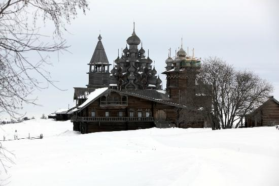 Boat Trip to Kizhi Island : Looking back across the snow, the peasant house is in front of the Transfiguration Church