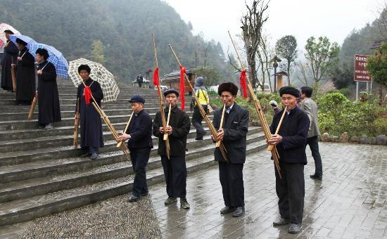 Xijiang Miao Nationality Village: Miao villagers playing instruments as tourists leave in the late afternoon