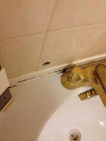 Churchills Hotel: Holes in the tiles and mouldy grout in the bathroom...