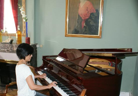 Chateau des Grandes Vignes: Lounge with grand piano and original paintings on wall