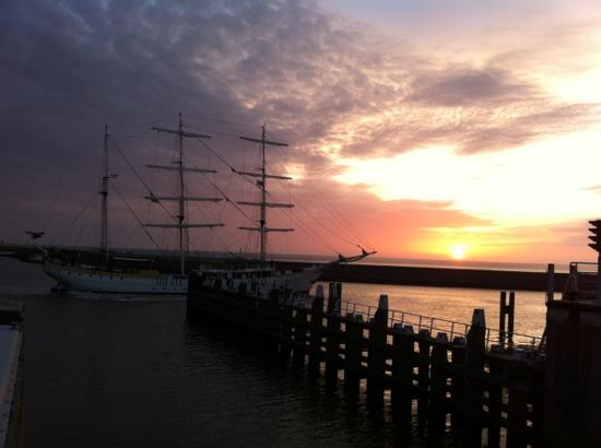Port of Harlingen: tall ship leaving the port at sunset