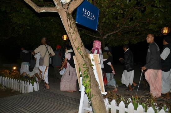 Isola Restaurant: photo taken from beachfront table with krishna followers passing by chanting