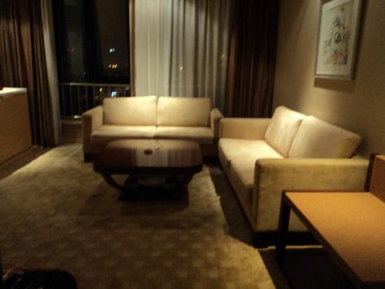 Baihuan Hotel: Sitting area with sofas and coffee table, window behind