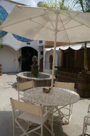 Hostal Punto 79: Mesas con sombrillas en la terraza