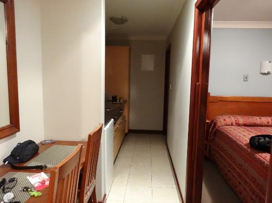 Quantum Lodge Motor Inn: couloir menant à la SDB avec la cuisine sur la gauche