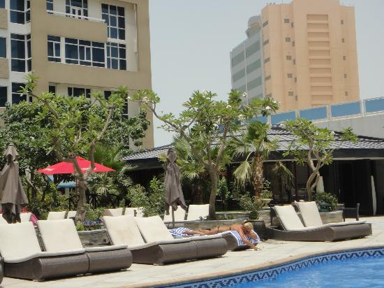 Elite Seef Residence & Hotel: Lounge Chairs by pool - breakfast restaurant is in the back