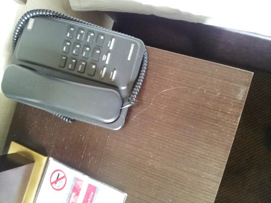Talbot Hotel Carlow: previous guests hair stuck to phone on badly worn nightstand.