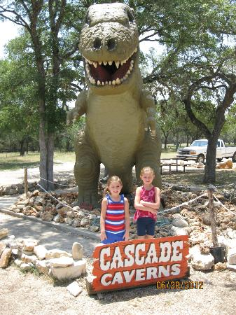 Cascade Caverns: My grand daughters in front of the dinosaur that was donated from Hollywood.