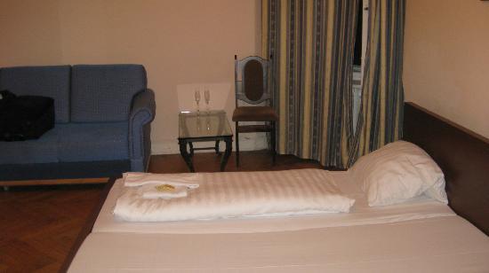 Hotel Central Inn: Schlaffzimmer mit Doppelbett, Sofa, Stühlen und Tisch