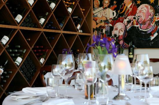 Friends Restaurant: Dining room, wine rack, artwork