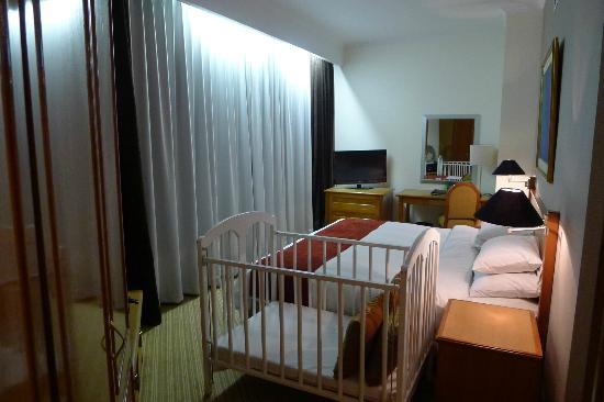 Hotel Menara Peninsula: Bed with optional baby cot
