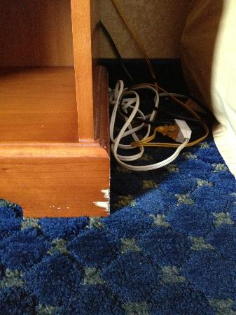 Quality Inn & Suites Phoenix: Chipped end-table with wire bundle, beside bed.