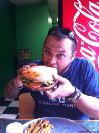 "Aardvark Kafe: my husband attempting the giant black bean burger called ""The Jen Burger"""