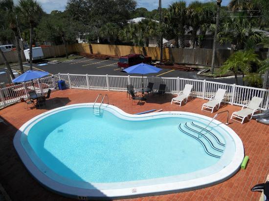 Rodeway Inn: Piscina del hotel mirada desde la terraza con quitasoles azules.