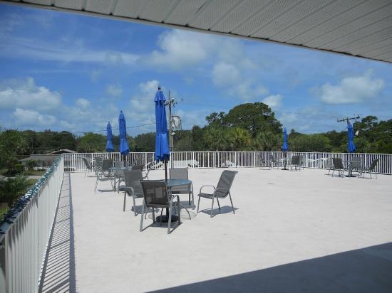 Rodeway Inn: Terraza del segundo piso del hotel con sillas, mesas y quitasoles azules.