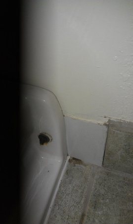 Farmington Inn: broken tiles around leaky toilet with mold