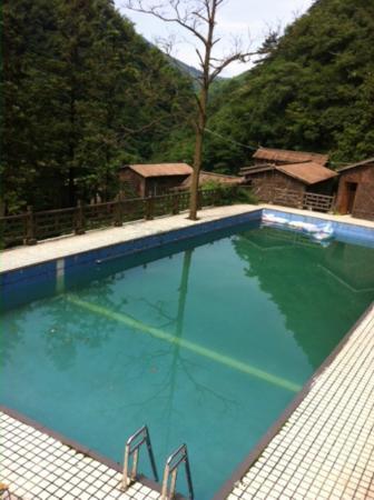 Jiulongxia Holiday Resort : Murky pool and outside huts