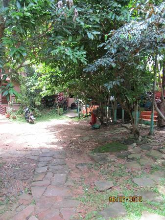Sakal Bungalows: Garden path past wooden bungalows to modern rooms