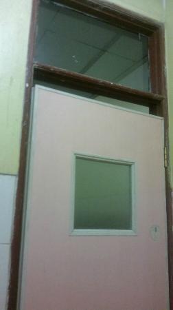 โรงแรมฮุสวาห์ทรานซิท: La puerta de madera mala y con huecos al pasillo.