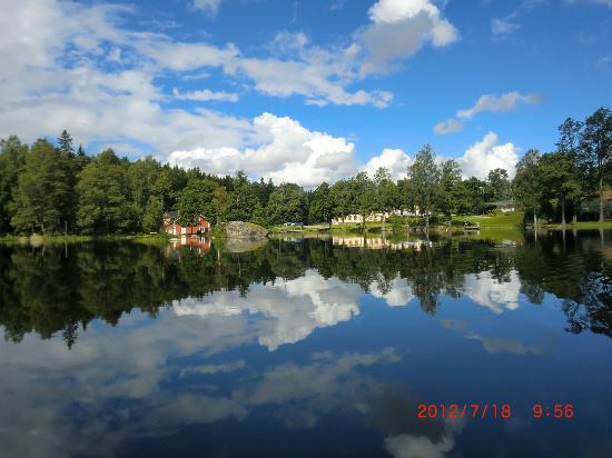 Hennickehammars Herrgard: En spegelblank bild av sjön och herrgården.