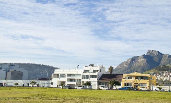 Dolphin Inn Guesthouse, Mouille Point: Guest house(yellow) with Cape Town Stadium in background
