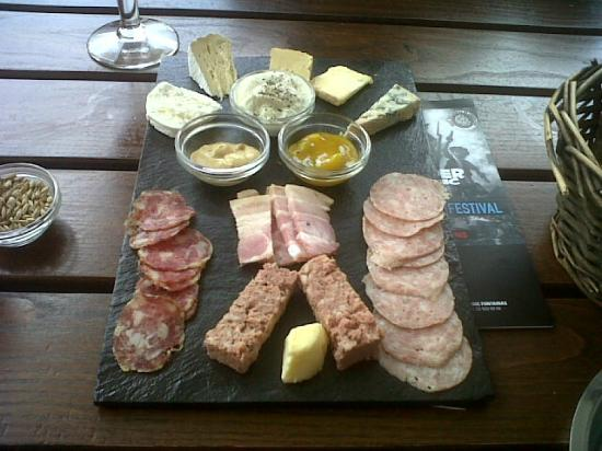 Moeder Lambic: Mixed cheese and meat platter served with brown sourdough bread.