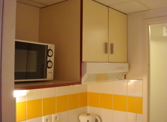 Appart'City Bordeaux Centre : Le micro-onde et le placard à vaisselle