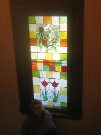 The Victoria Inn: my husband standing at the top of the stairs, taking a pic of me in front of stained glass windo