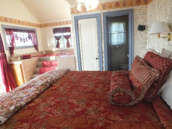 ويلر أون ذا باي لودج آند مارينا: The bed, bathroom door and elevated, deep, Jacuzzi bathtub 