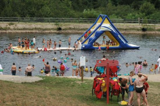 Liquid Planet Water Park : Man made murky pond with inflatable slide
